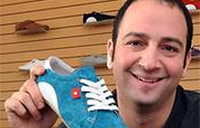 photo of Tal Dehtiar holding a blue running shoe