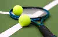 Two tennis balls and a tennis raquet on a tennis court