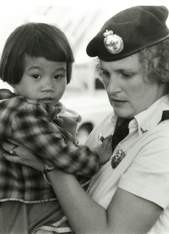 A child Indochinese refugee being assisted