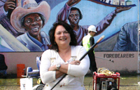 Judy Baca standing before one of her mural works