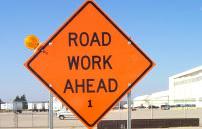Orange sign saying road work ahead