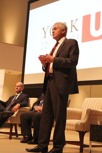 York University President Mamdouh Shoukri speaks at the Town Hall. York Vice-President Finance and Administration Gary Brewer (seated) looks on.