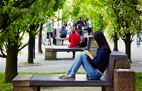Student relaxes under canopy of trees