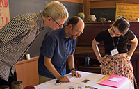 City curator Wayen Reeves (centre) discussing some photgraphs with a visitor at Zion Schoolhouse. Craig Heron is on the left