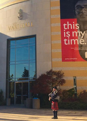 A lone piper plays outside Vari Hall
