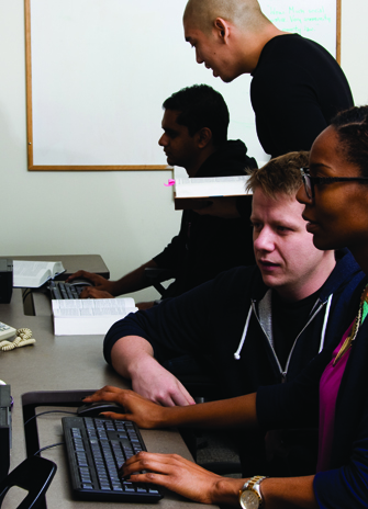 two young people are looking at a website using a desktop computer