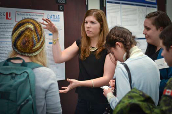 Jennifer Della Mora presents her poster on the Search for the Magnetic Monopole during the conference poster
