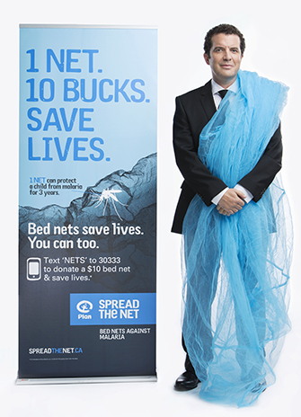 Rick Mercer with a bed-net drapped over one shoulder