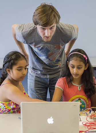 York U Digital Media student Michael Stuart helps Summer Inventor Workshop participants at the Gore Meadows branch of the Brampton Library.