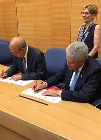 York University President and Vice Chancellor Mamdouh Shoukri (right) signs a memorandum of understanding with Tel Aviv University President Joseph Klafter, while Ontario Premier Kathleen Wynne looks on.