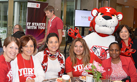 Dressed in their red and white garb, staff and faculty alumni and donors enjoy the buffet spread (with a little help from one of the York Lions mascots) at the campus breakfast