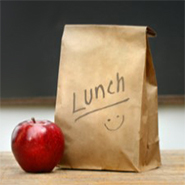 a brown bag with an apple beside it