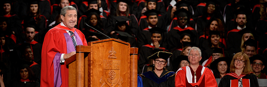 Bill Fisch stands at the podium on the convocation stage.