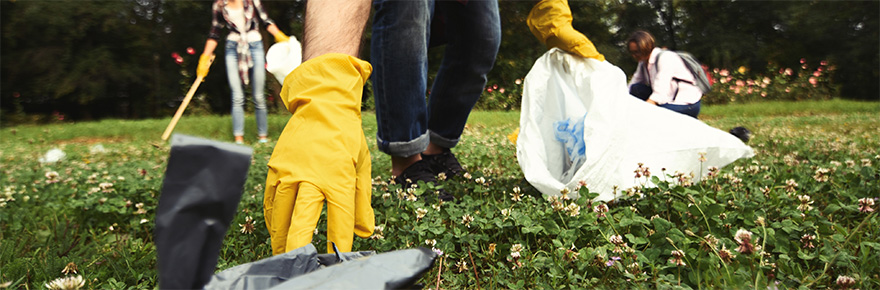 A person picking up garbage in a field