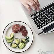 A plate of healthy food next to a computer