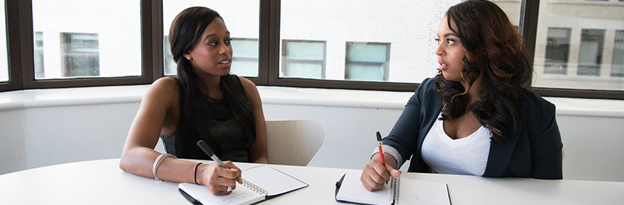 Two Black women talk together