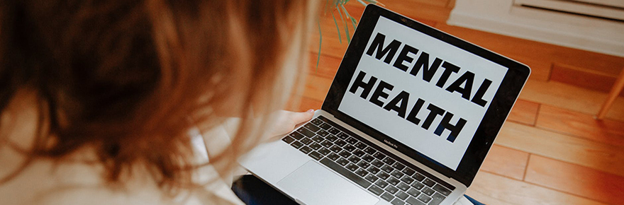 """A woman looking at a laptop that says """"Mental Health"""""""