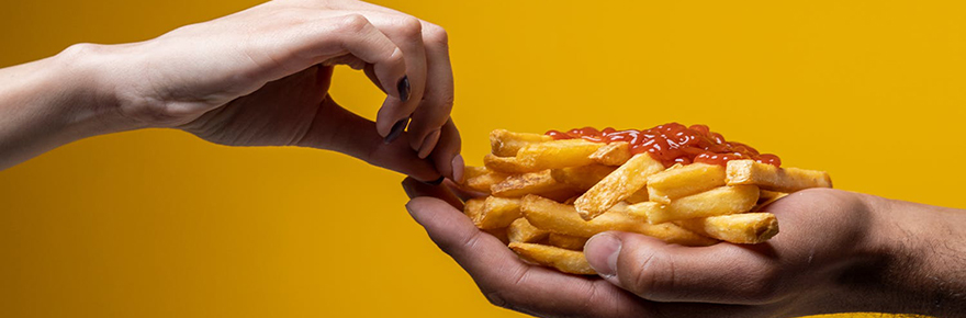 A woman's hand reaching for french fries out of a man's hand