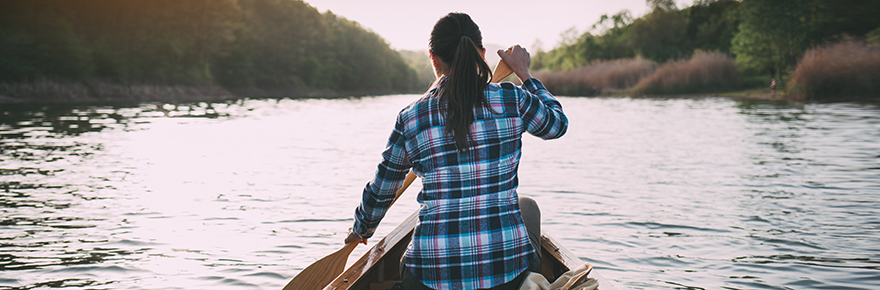 A woman paddles a canoe on a freshwater lake FEATURED