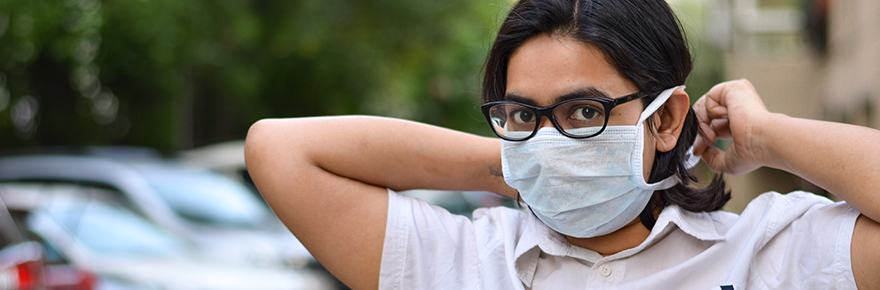 A young woman dons a mask to protect against the novel coronavirus FEATURED image for York library story