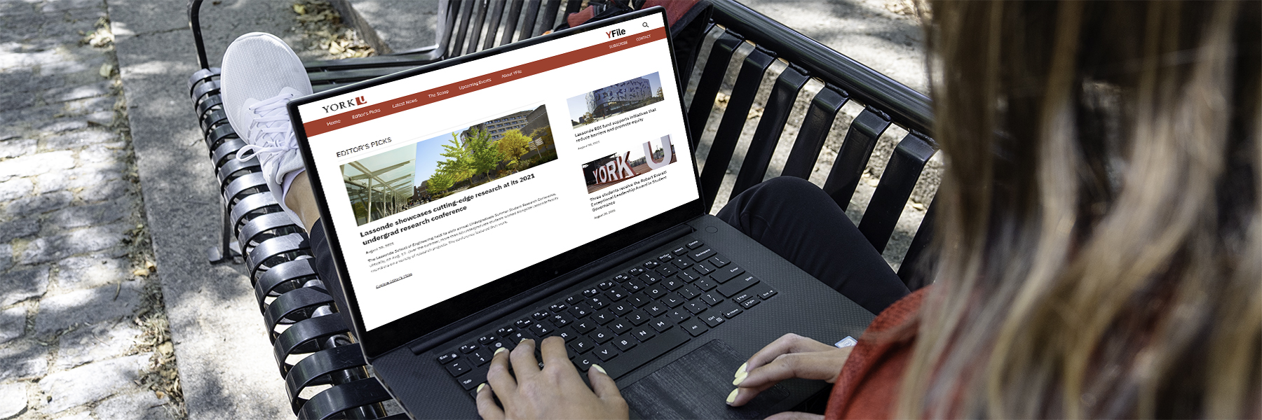 An image of a woman with a laptop that shows the YFile website