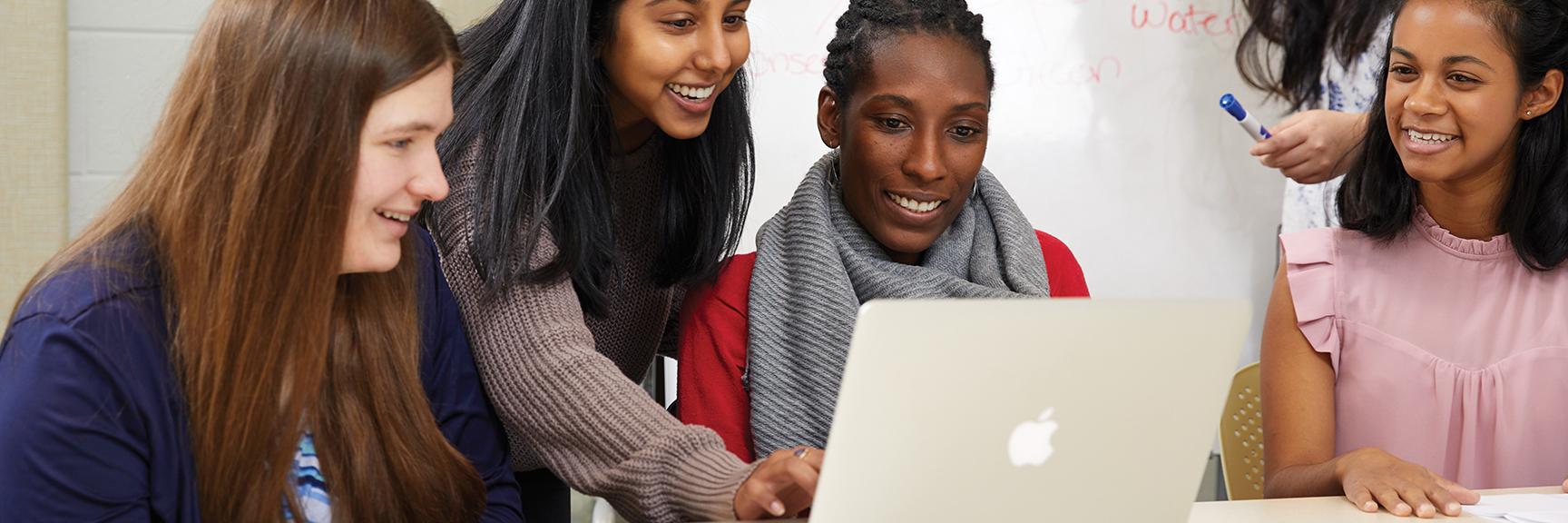 Students huddled around a laptop